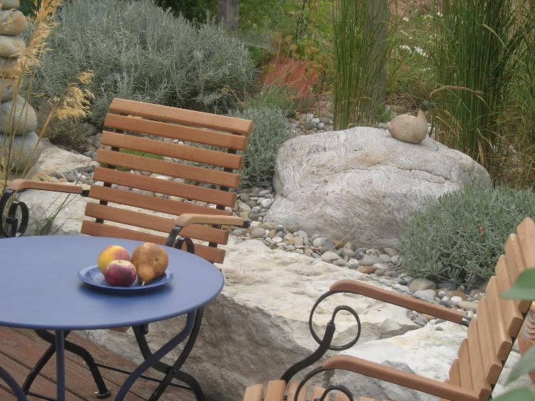 Einladendes Gartenbild mit romantischen Gartenmöbeln und gelungener Gestaltung mit Steinen