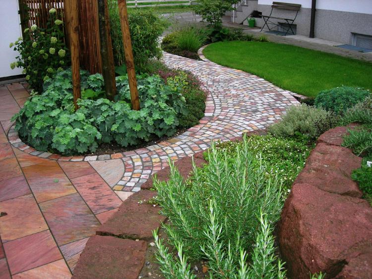 Quarzitpflaster in Segmentbogenform und rosa Quarzit-Terrassenplatten. Kleine Pflanzinsel mit Hausbaum, Alchemilla und Bambus (Fargesia)