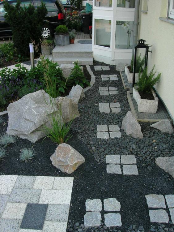 Schwarzer Basaltschotter und graue, formwilde Granitsteine führen mit Trittplatten zum Eingang