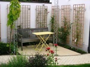 Kleiner romantischer Sitzplatz mit Holzspalieren für Rosen und Clematis. Gartengestaltung in Freiburg, Helmut Lamprecht