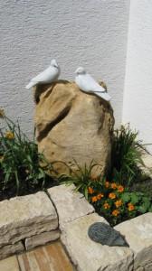 2 weiße Tauben aus Stein sitzt auf einem Naturstein-Findling