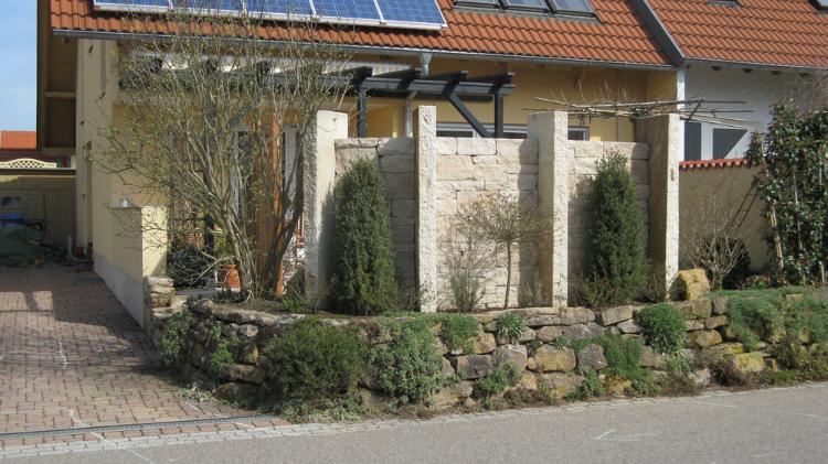 Sichtschutzlösung aus Natursteinstelen und Römermauerk in Vörstetten.