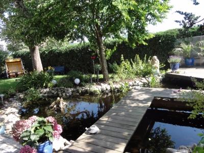 Gatenteich mit einem darüber führenden Holzsteg. Buddha-Statue in Pflanzen eingebettet