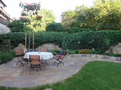 Gartensitzplatz aus polygonal verlegten Porphyrrplatten. Eingefasst mit einer Muschelkalkmauer. Gartenplanung Helmut Lamprecht