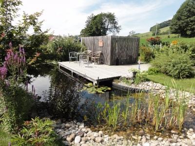 Ein über dem Wasser/Teich schwebendes Holzdeck und origineller Sichtschutz aus Douglasie.