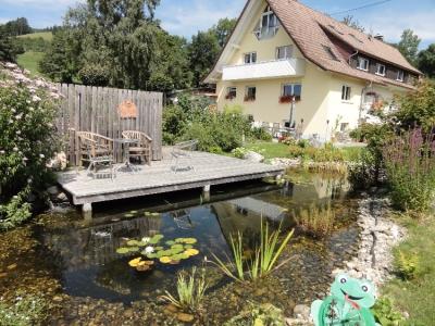 Ein über dem Wasser/Teich schwebendes Holzdeck in St. Peter/ Schwarzwald. Gartenplanung Helmut Lamprecht.