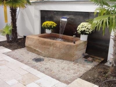 Gartengestaltung im mediterranen Stil.  Hanf-Palmen, Sandstein-Brunnen mit Wasserspiel, Mauer mit Corten-Stahlwand. Gartenplanung für einen Hausgarten in Breisach. Helmut Lamprecht