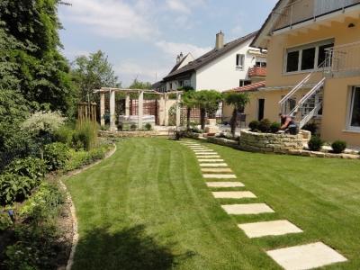 Stimmungsvolle Gartengestaltung mit geschwungenem Plattenweg, Natursteinmauern, Palmen und einer schönen Holzpergola-Laube. Gartenplanung Helmut Lamprecht