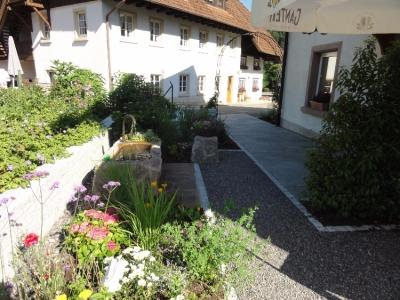 Eingang gestaltet mit Natursteinplatten, Granitmauern, Sandsteinbrunnen und ganz vielen Bauerngartenstauden
