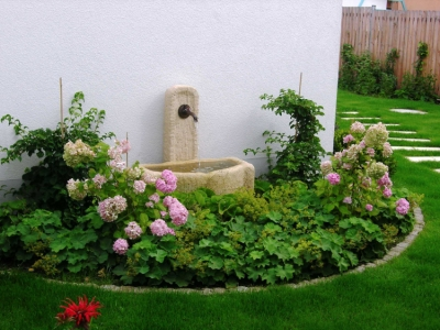 Brunnenbecken und Hortensien und Stauden vor einen Garagenwand. Gartengestaltung im Detail von Helmut Lamprecht