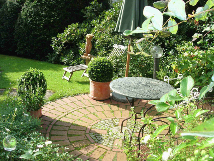 Kleiner runder Sitzplatz aus Klinker-pflaster und Granit-steinen in einem formalen Garten.