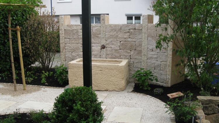 Dietfurther Rebmauerwerk von Frankenschotter und Sandsteinstelen mit einem Wasserbrunnen in Vörstetten. Gartenplanung Helmut Lamprecht