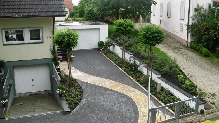 Ein geschwungener Pflasterweg führt durch die große Garageneinfahrt elegant zum Hauseingang . Gartenplanung in Ebringen, Helmut Lamprecht