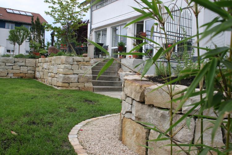 Gartenoase in Heitersheim. Natursteinmauern aus Sandstein. Kräuterspirale